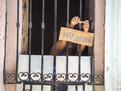 A woman hangs a sign advertising food in Havana.