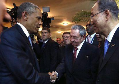 Barack Obama greets Raúl Castro.