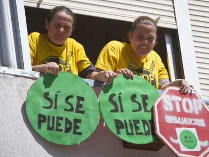 The Huelva woman saved from eviction, María del Carmen Andújar Hidalgo (l), and her sister hang placards from the window of the embargoed flat.