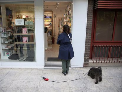 A client waits outside a pharmacy in downtown Madrid.