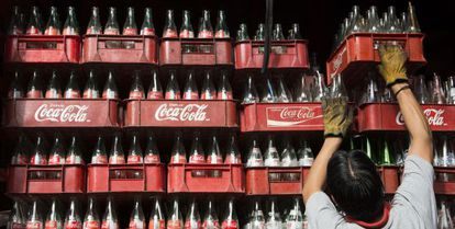 A worker stacks crates of empty Coca-Cola bottles in México.