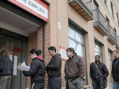 People standing in line outside an unemployment office in Alcalá de Henares (Madrid).