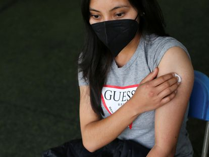 A woman sits after receiving a dose of the Pfizer vaccine against Covid-19 in in Xochimilco, on the outskirts of Mexico City.