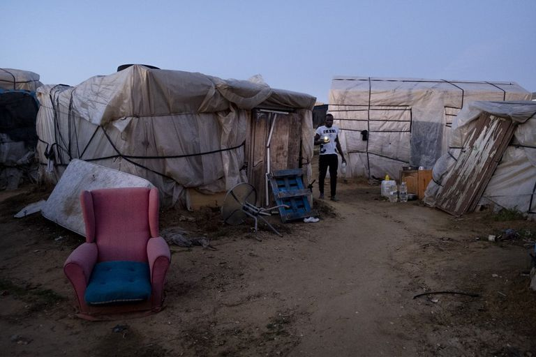 A field worker walks between shacks at the makeshift camp in Lepe.