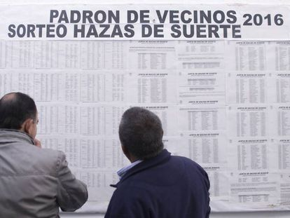 Locals check their names on the 'lucky lands' land raffle in Vejer de la Frontera.
