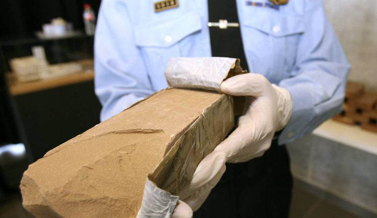 An officer with a heroin package seized during a drug haul in Catalonia in 2014.