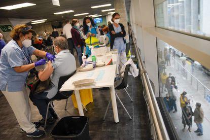 Sanitarios vacunan este viernes con dosis de AstraZeneca en el WiZink Center de Madrid.