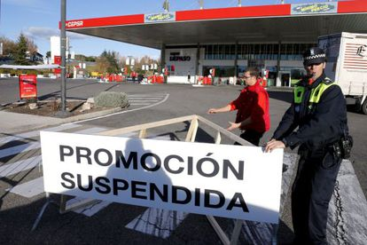"""""""Offer suspended,"""" reads this sign, as police close of the gas station offering free fuel."""