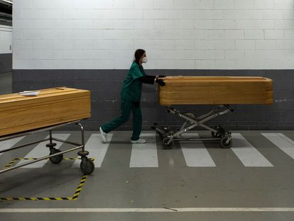 A worker at a funeral home moving the coffin of a coronavirus victim.