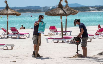 Two workers on Alcudia beach in Mallorca.