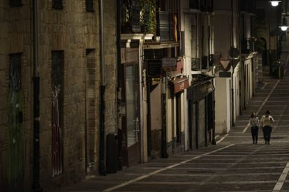 Residents wearing face mask walk along an empty street in Pamplona on October 24.